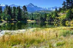 Lago y montañas nevadas durante la estación de follaje Imagen de archivo libre de regalías
