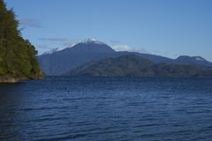 Lago Yelcho. In the Aysen Region of southern Chile. Large body of fresh water surrounded by lush forest and snow capped mountains royalty free stock photo