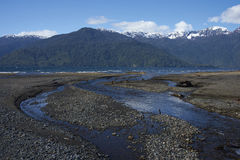 Lago Yelcho. Stream running into Lago Yelcho in the Aysen Region of southern Chile. Large body of fresh water surrounded by lush forest and snow capped mountains royalty free stock photo
