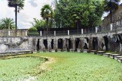 Lagoa artificial completamente da vegetação com as paredes que formam a caverna de pedra foto de stock royalty free