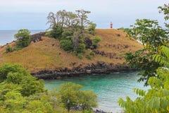 Lagoa Azul Blue Lake en härlig strand med baobaben och en fyr upp klippan i São Tomé och Príncipe - Afrika arkivbilder