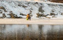 A lagoa começa na primavera a derreter e todo o pescador trava um peixe Foto de Stock