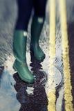 Lagoa de água tocante da pessoa nas botas de borracha Foto de Stock Royalty Free