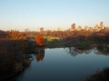 Lagoa do Central Park com construções de Autumn Trees e da cidade Imagens de Stock Royalty Free