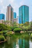 Lagoa e flamingos no parque de Kowloon com arranha-céus atrás imagens de stock