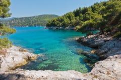 A lagoa pequena com pinheiros e as rochas sobre a turquesa claro molham perto do cabo Amarandos na ilha de Skopelos foto de stock