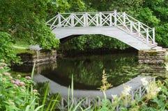 Lagoa pequena e ponte de madeira branca decorativa fotografia de stock