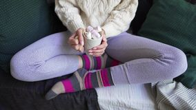 Lagom or Hygge concept. A woman in beautiful warm multi-colored socks and pajama pants holds a hot cup of coffee in her. Hands. 4k stock video footage