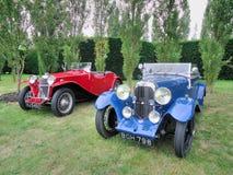 Lagonda azul clásico y Riley rojo fotos de archivo libres de regalías