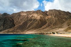 Lagoon with a coral reef against the backdrop of high mountains and a blue sky with white clouds in Egypt Dahab South Sinai stock image
