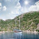 Lagoon, sailing ship and mountainous Stock Image
