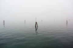 The Lagoon in Venice in a winter foggy day, no boats around Royalty Free Stock Photography