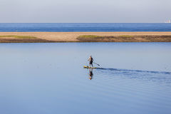 Lagoon Water Paddler SUP. SUP Paddler on board paddling on blue lagoon river water scenic beach ocean landscape Royalty Free Stock Images