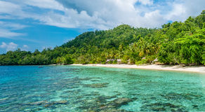 Lagoone and Bamboo Huts on the Beach, Coral Reef of Yananas Homestay Gam Island, West Papuan, Raja Ampat, Indonesia.  Stock Photography