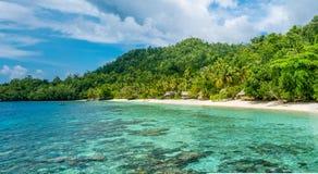Lagoone e capanne di bambù sulla spiaggia, Coral Reef dell'alloggio presso famiglie Gam Island, Papuan ad ovest, Raja Ampat, Indo Fotografia Stock
