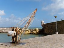 LAGOS, ALGARVE/PORTUGAL - MARCH 5 : Old Crane outside Fort Ponta Royalty Free Stock Photos