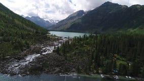 Lagos turquoise con una pequeña cascada entre ellos, entre las montañas de Altai almacen de metraje de vídeo