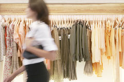 Lagra assistenten som går av hängande kläder i lager Royaltyfri Bild