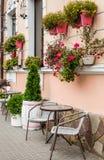 Lagra framdelen av en blomsterhandel med tabellen och chears som säljer trädgårds- växter arkivbild
