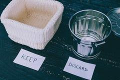 Lagringskorgen och gargabe slänga i soptunnan för att välja vilka objekt som ska hållas och vilket som ska kasseras, declutterbeg fotografering för bildbyråer