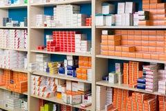Lagringssystem av det moderna apoteket med gods i hyllor Arkivfoton