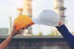 Lagteknikerhand som rymmer säkerhetshjälmen på oljeraffinaderibakgrund royaltyfria bilder