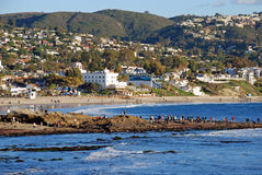 Laguna Beach, California tide pool exploring at Main Beach rocks with Hotel Laguna in background. People are seen exploring rocks and tide pools on rocks near Royalty Free Stock Photo