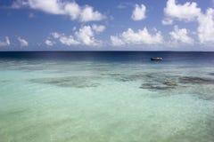 Laguna di Calmness con la piccola barca sull'orizzonte immagine stock libera da diritti