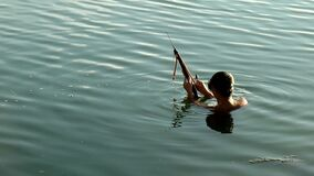 Sling arrow lake diver. Laguna, Philippines – June 5, 2015: Lake diver uses improvised sling arrow to catch fish stock video footage
