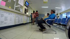 People seated in Government vehicle licensing office. Laguna, Philippines - April 1, 2016: people seated patiently waiting in Government licensing office for the stock footage