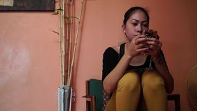 Lady uses cell phone to communicate at home. Laguna, Philippines - August 2, 2015: Lady uses smart phone to communicate at home stock video footage