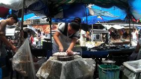 Milk Fish is chopped at messy street wet market