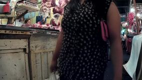Woman passes by in a messy flea market stalls selling pork