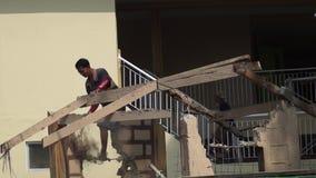 Carpenter demolish roof trusses with hammer
