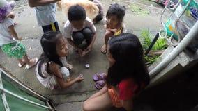 Children playing round cards in slum community stock footage