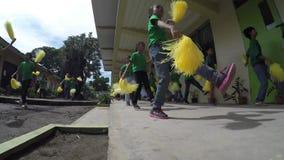 School children perform pom poms calisthenics. Laguna, Philippines - September 3, 2015: Public elementary grade school pupils perform dance exercise, a yearly stock footage
