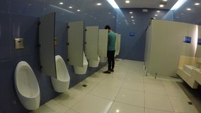 Young man using mall public urinal. Laguna, Philippines - September 19, 2015: Young man uses public urinal in huge commercial building stock footage