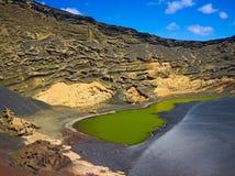 Laguna Verde (den gröna lagun) på vatten för El Golfo är en fullständig kontrast till den svarta sanden och röd, apelsinen och gu Royaltyfri Foto