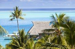 Lagune bleue de l'île de Bora Bora, Polynésie Une vue de taille sur des palmiers, des loges traditionnelles au-dessus de l'eau et Image stock