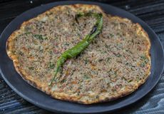 Lahmacun traditional turkish pizza. With minced beef or lamb meat on dark table background Royalty Free Stock Photos