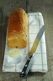 Laib des Brotes mit Messer und Butter Stockfotografie