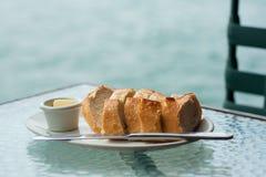 Laib des Sauerteigbrotes mit Butter auf Glastisch Lizenzfreie Stockfotografie