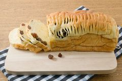 Laib geschnitten vom Rosinen-Brot auf einem hölzernen Schneidebrett Lizenzfreie Stockfotografie