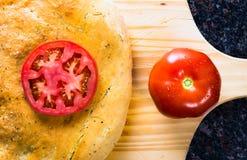 Laib von Focaccia-Brot mit Tomaten. Stockfotos