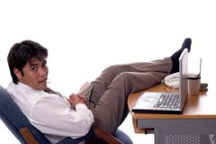 Laid back. Young asian businessman kicking his feet up at work Royalty Free Stock Image