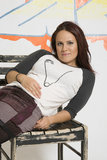 Laid Back. Young woman laid back on a chair in front a of graffitied wall Stock Photography