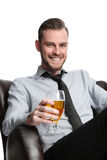 Laid back businessman with beer. A businessman sitting down relaxing in a lounge chair with a beer. Looking at camera with white background Stock Photos