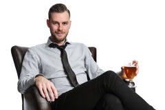 Laid back businessman with beer. A businessman sitting down relaxing in a lounge chair with a beer. Looking at camera with white background Royalty Free Stock Image