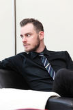 Laid back businessman sitting down. A relaxed businessman sitting down in an arm chair, in a lounge room wearing a shirt and tie Royalty Free Stock Images