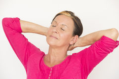 Laid back mature woman closed yes. Portrait attractive senior woman with arms up and hands in neck, relaxed, happy and daydreaming with closed eyes, isolated on Stock Photography